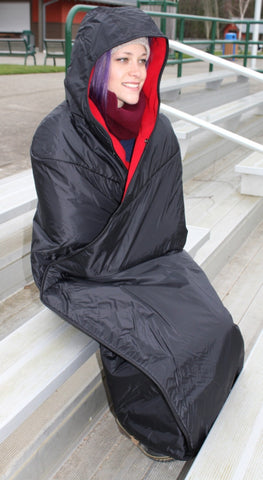 Mambe waterproof fleece Hooded Blanket - wrapping model head to toe, seated in stadium seating.