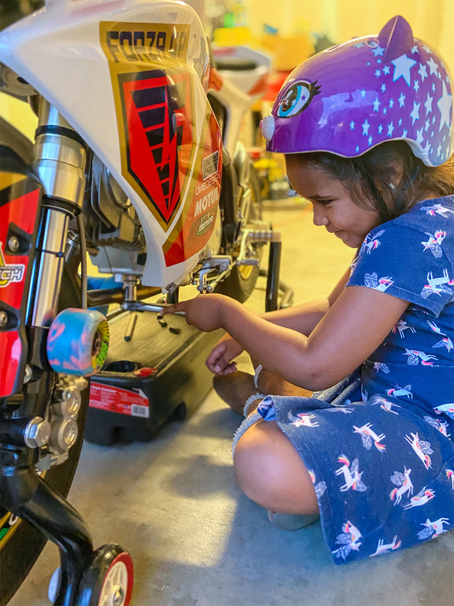 Harmony Grace Castille wrenching on her motorcycle