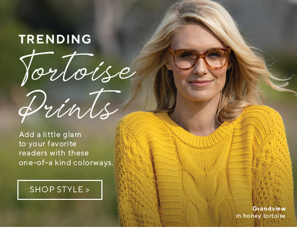 A blonde woman in yellow wearing Grandview blue light reading glasses in honey tortoise by Peepers