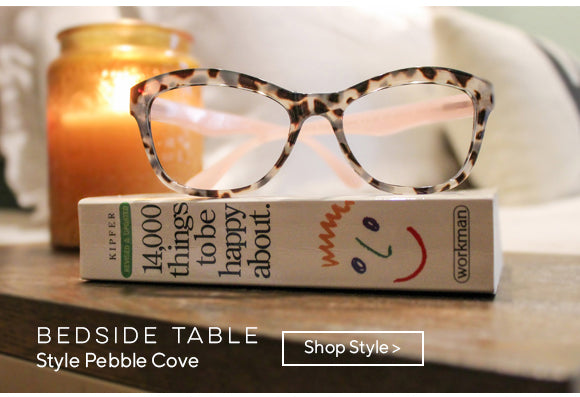 Peepers Pebble Cove reading glasses sitting on a bedside table on top of 14,000 Things To Make You Happy book