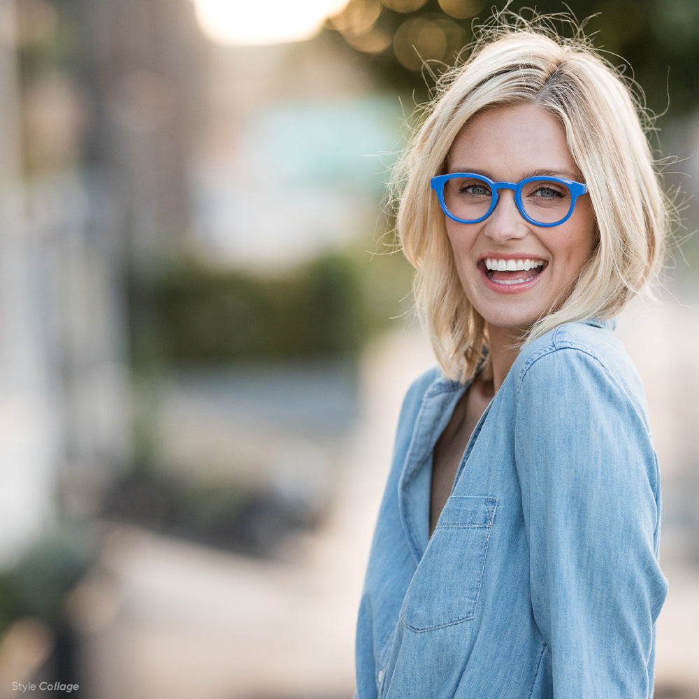 Blonde woman wearing Collage blue light reading glasses by Peepers outside in a denim shirt