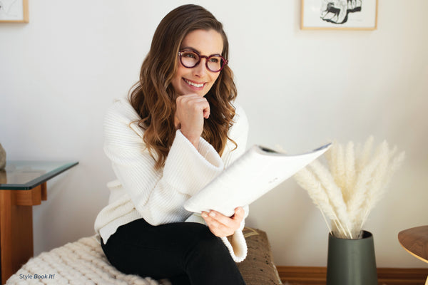 Brunette woman in white wearing Peepers reading glasses and reading