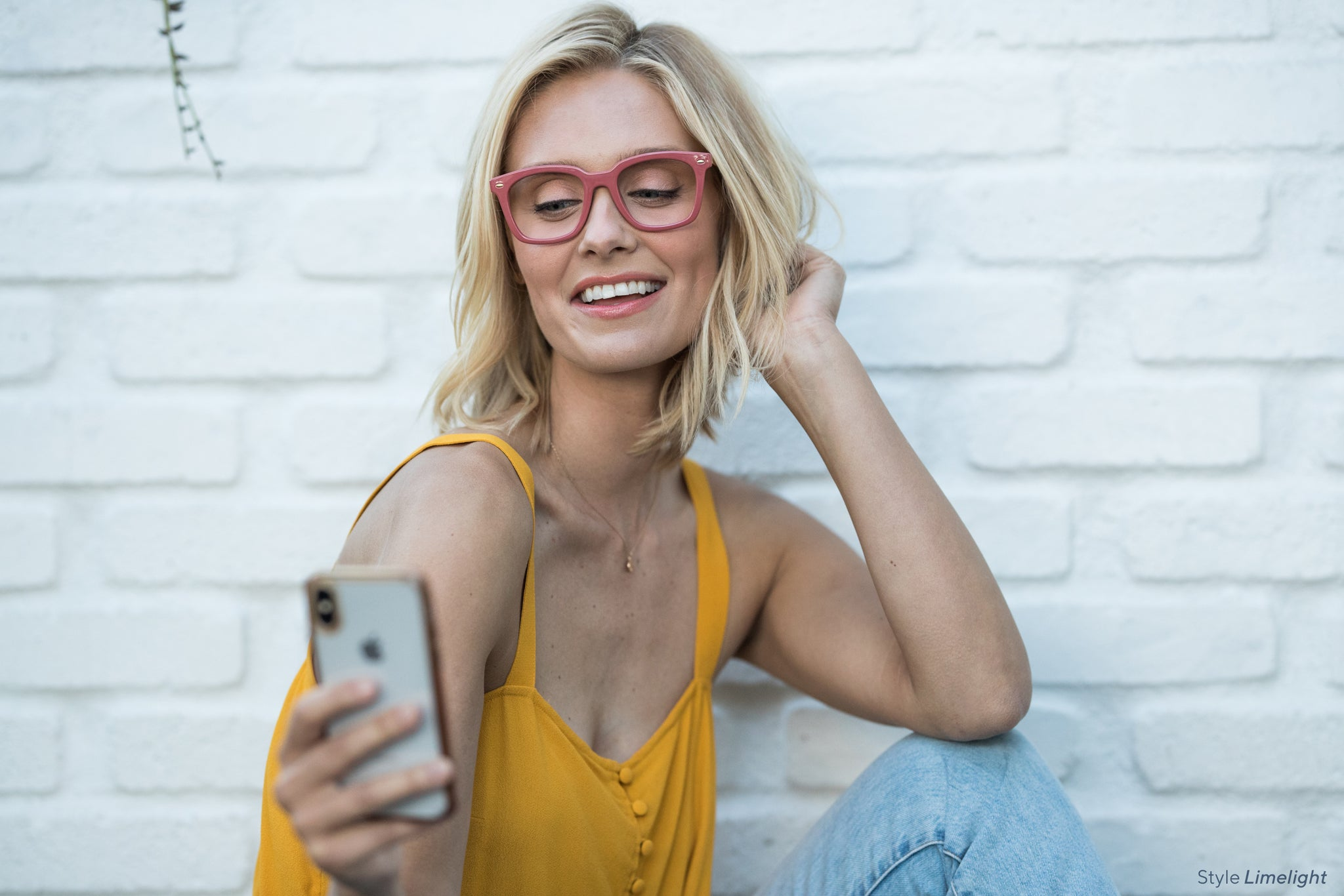 Blonde woman taking a selfie in front of a white brick wall while wearing Oprah's favorite Limelight blue light reading glasses by Peepers