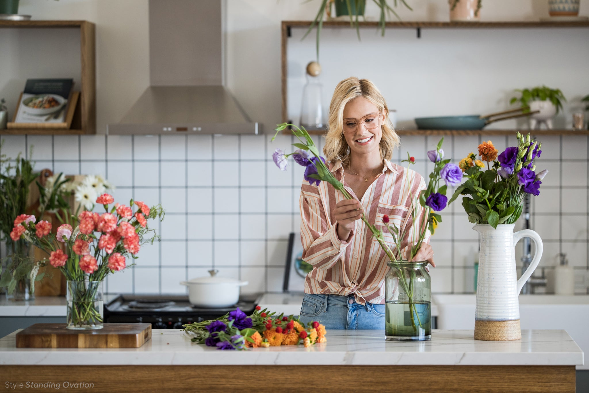 Blonde woman arranging flowers in her kitchen and wearing Peepers Standing Ovation blue light reading glasses