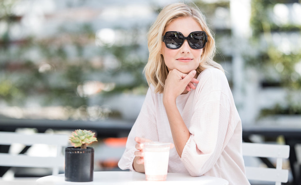 Blonde woman sitting in outdoor cafe wearing Peepers Carmen sunglasses