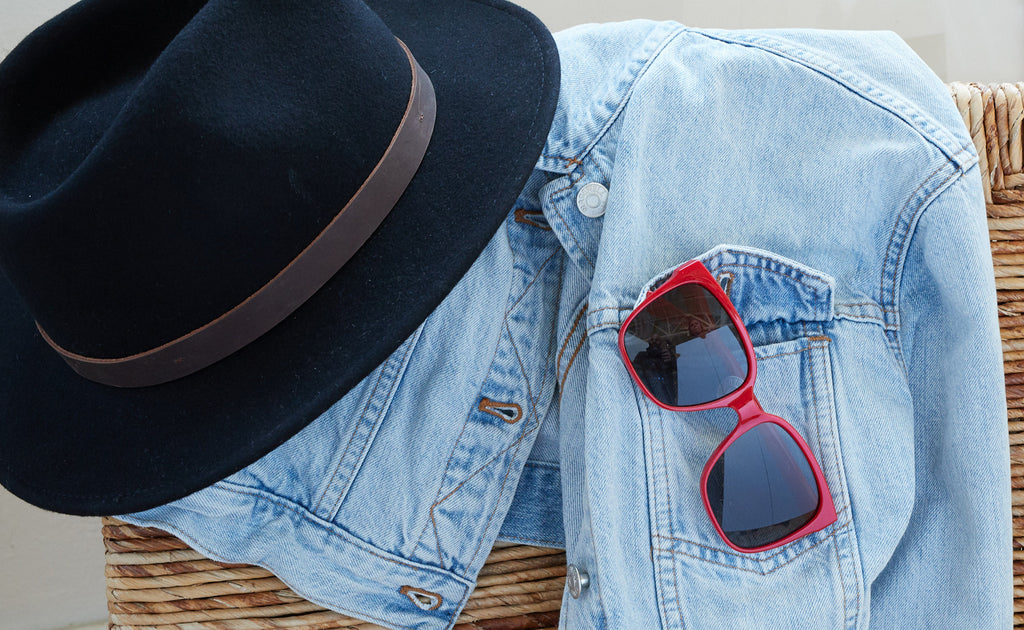 Jean jacket and hat draped over a chair with Peepers Palisades sunglasses in the pocket