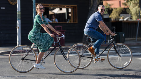 Man and woman riding bikes wearing Peepers sunglasses