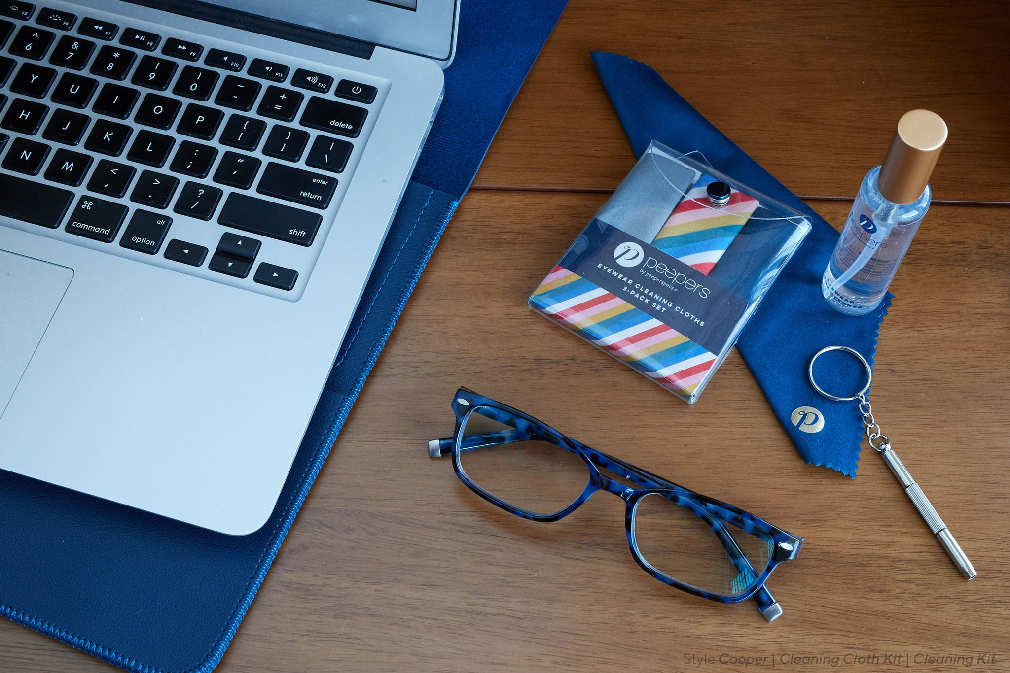 Peepers blue light reading glasses sitting next to a laptop with a cleaning cloth kit and cleaning kit
