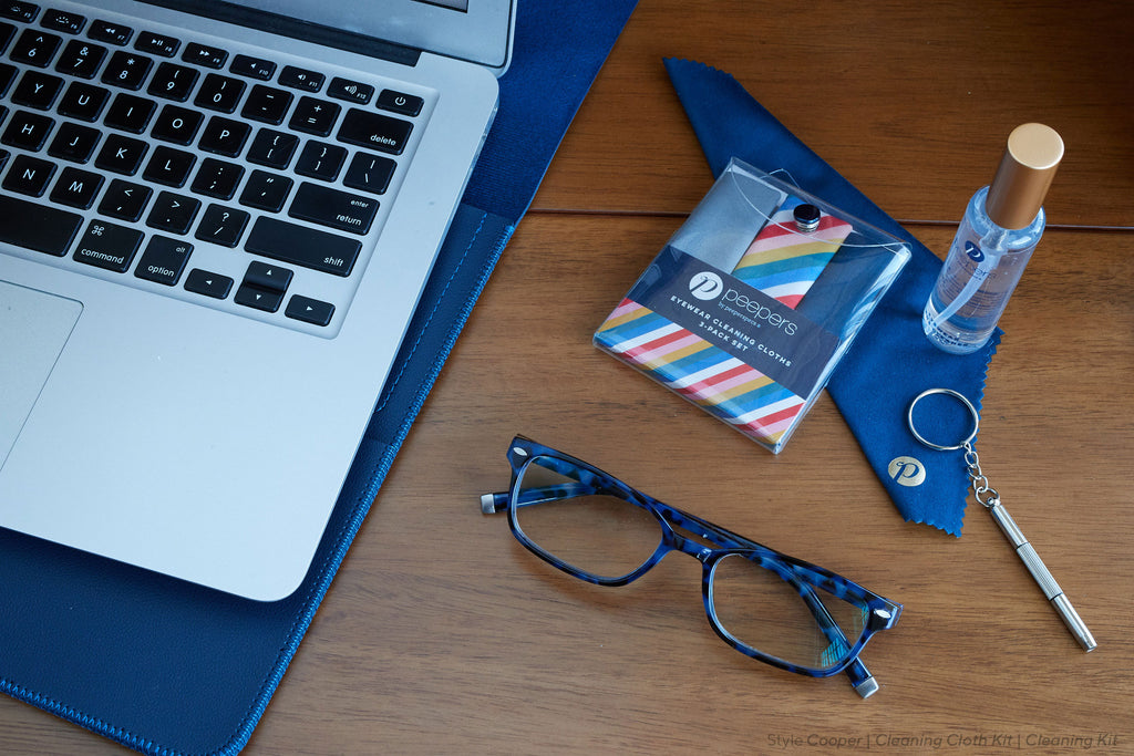 Open laptop next to Peepers cleaning kit and Cooper blue light reading glasses on a desktop