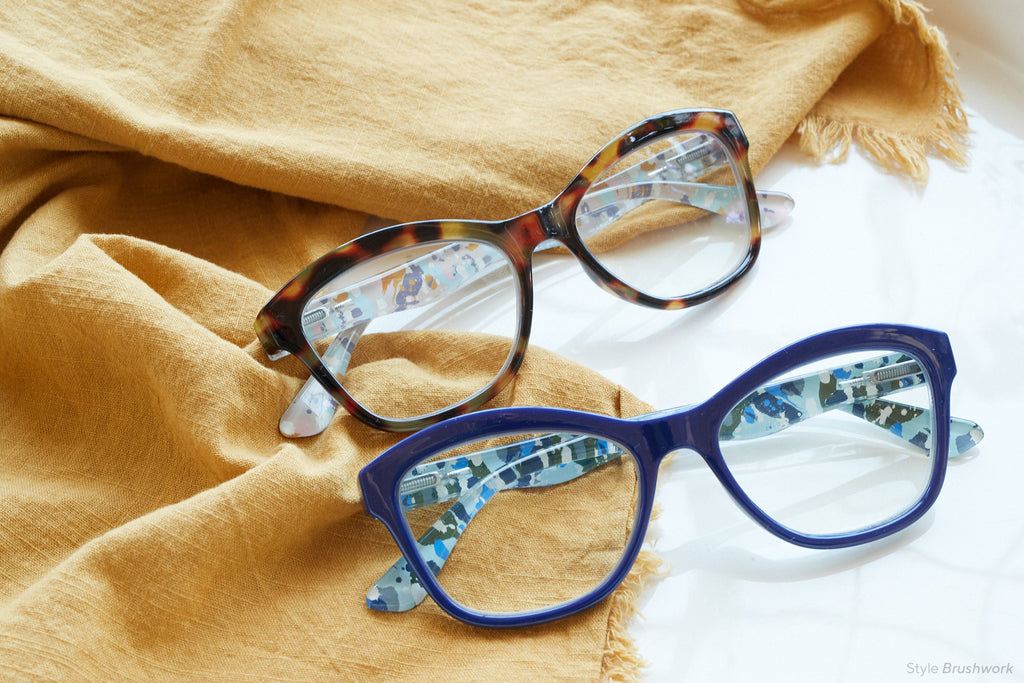 Brushwork Peepers blue light reading glasses folded flatlay on mustard gold cloth