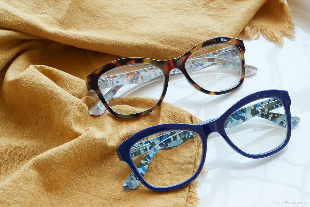 Peepers Brushwork blue light reading glasses folded on a mustard yellow cloth