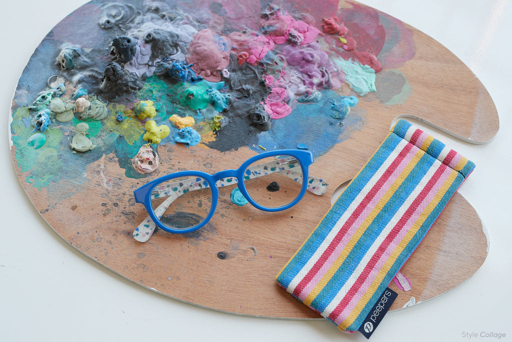 Peepers Collage blue light reading glasses with striped canvas case on an artist's paint pallette