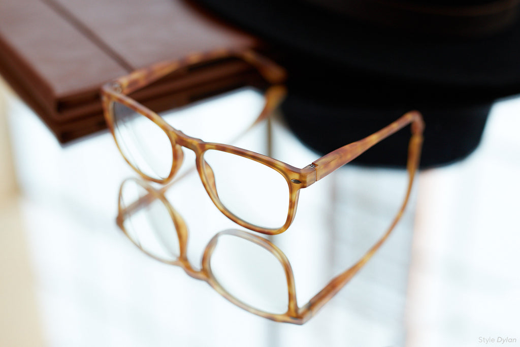 Peepers Dylan blue light reading glasses in honey tortoise sitting on a mirrored surface