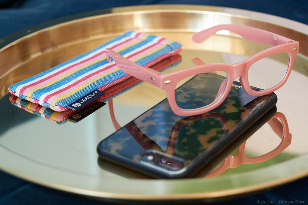 Lois blue light reading glasses by Peepers sitting on a phone on a table with a striped canvas case