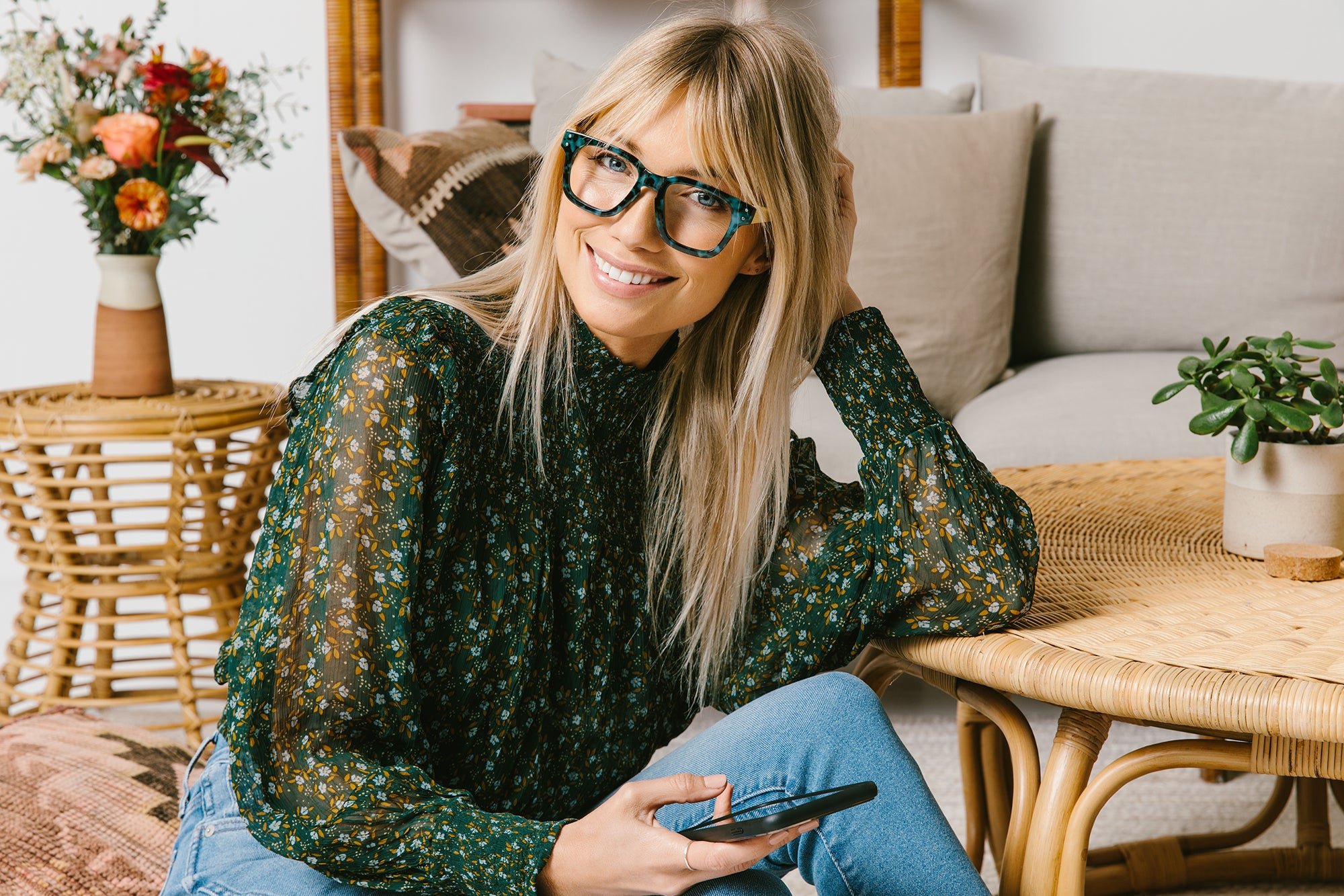 Woman dressed in green wearing Peepers Coffee Shop blue light reading glasses