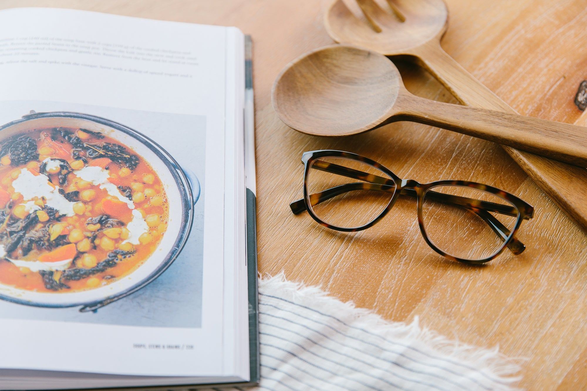 Peepers blue light reading glasses next to cookbook and utensils