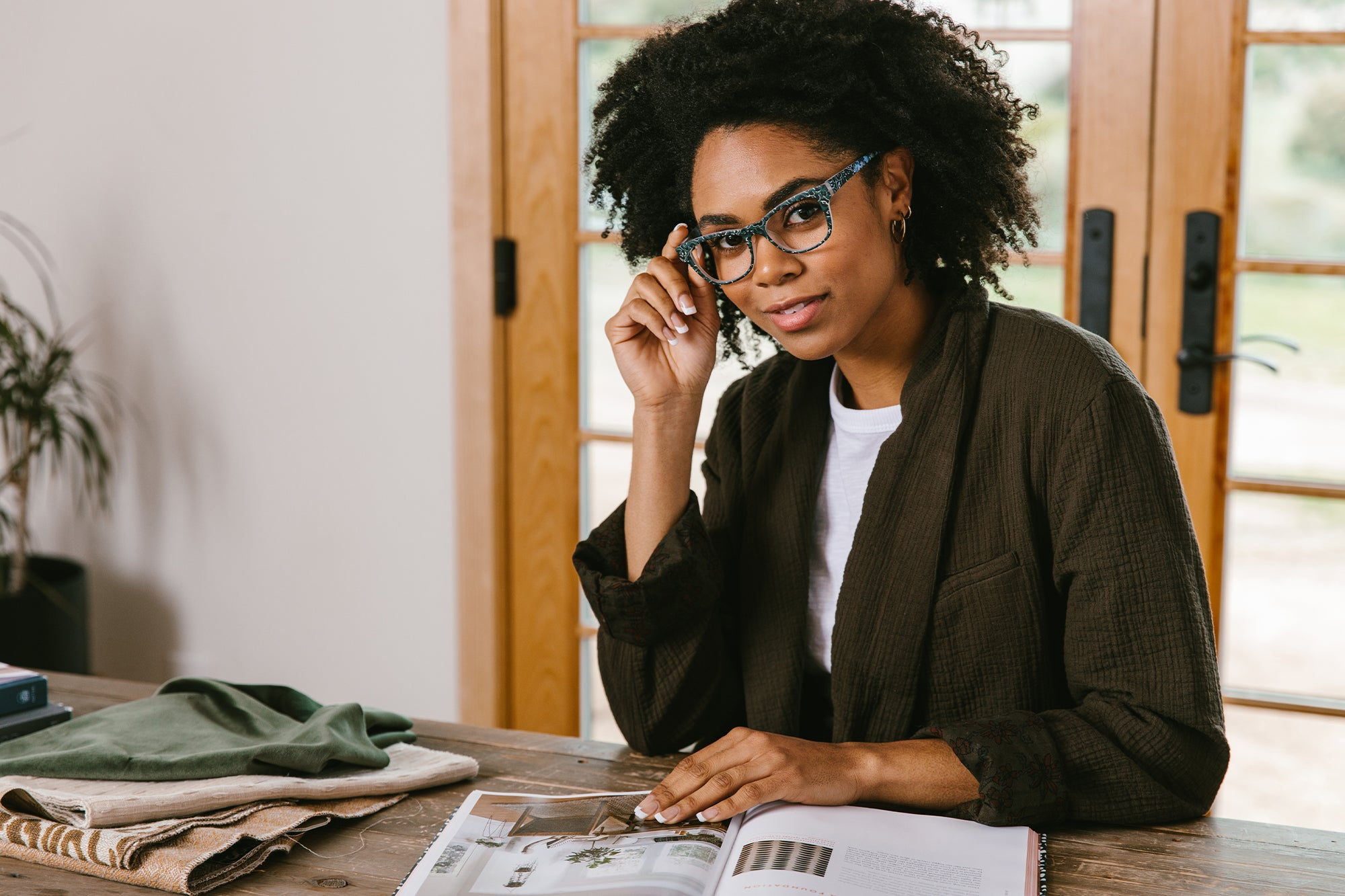 Woman wearing Peepers reading glasses while working from home