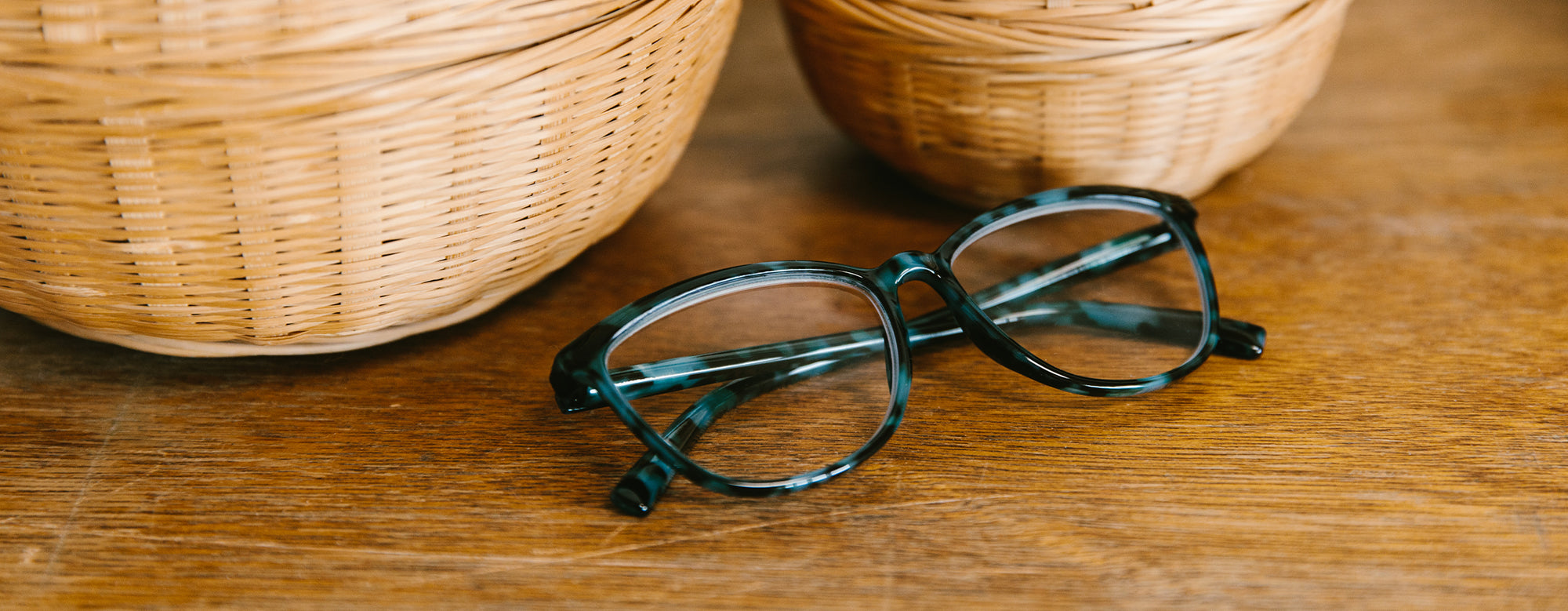 Peepers Bengal blue light reading glasses folded on a wooden table