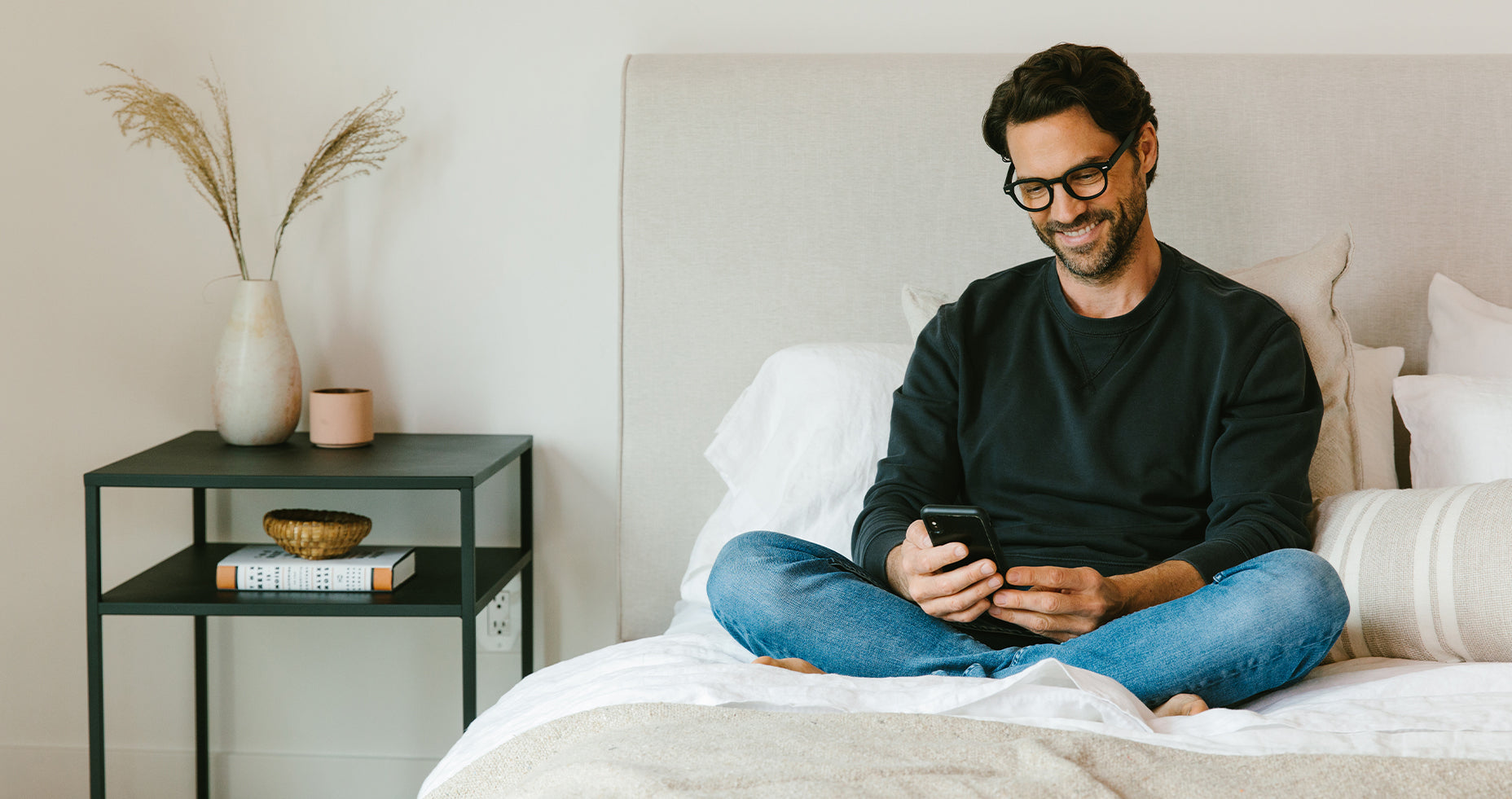 Man sitting on a bed looking at a phone