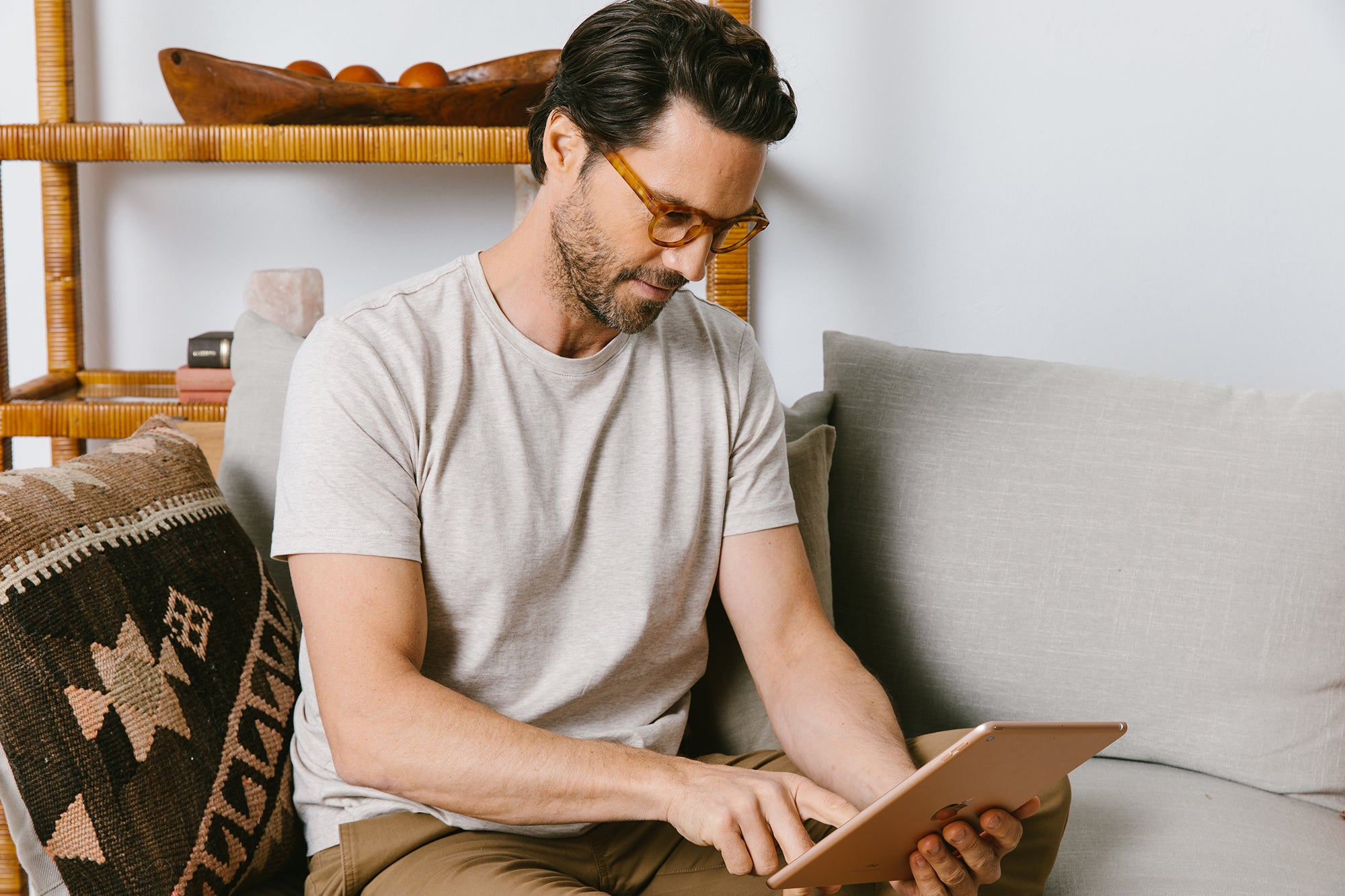 Man wearing Peepers blue light reading glasses while working on a tablet