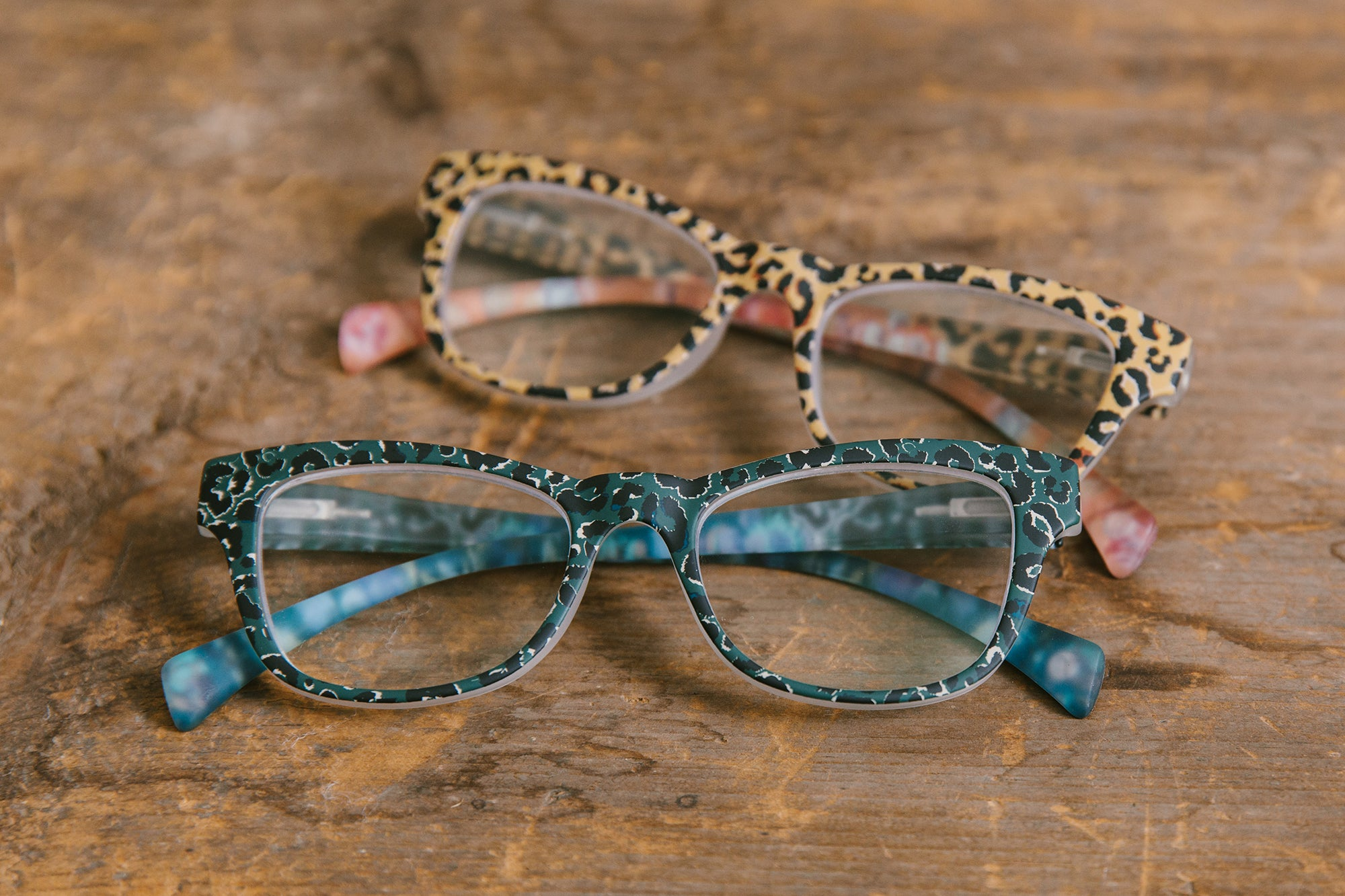 Peepers blue light reading glasses sitting on wood table