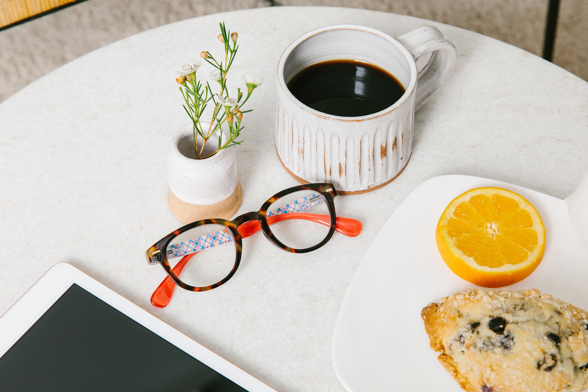 Peepers blue light reading glasses sitting on a table with breakfast