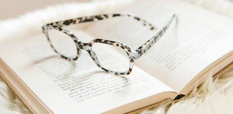 Peepers gray tortoise reading glasses on a book