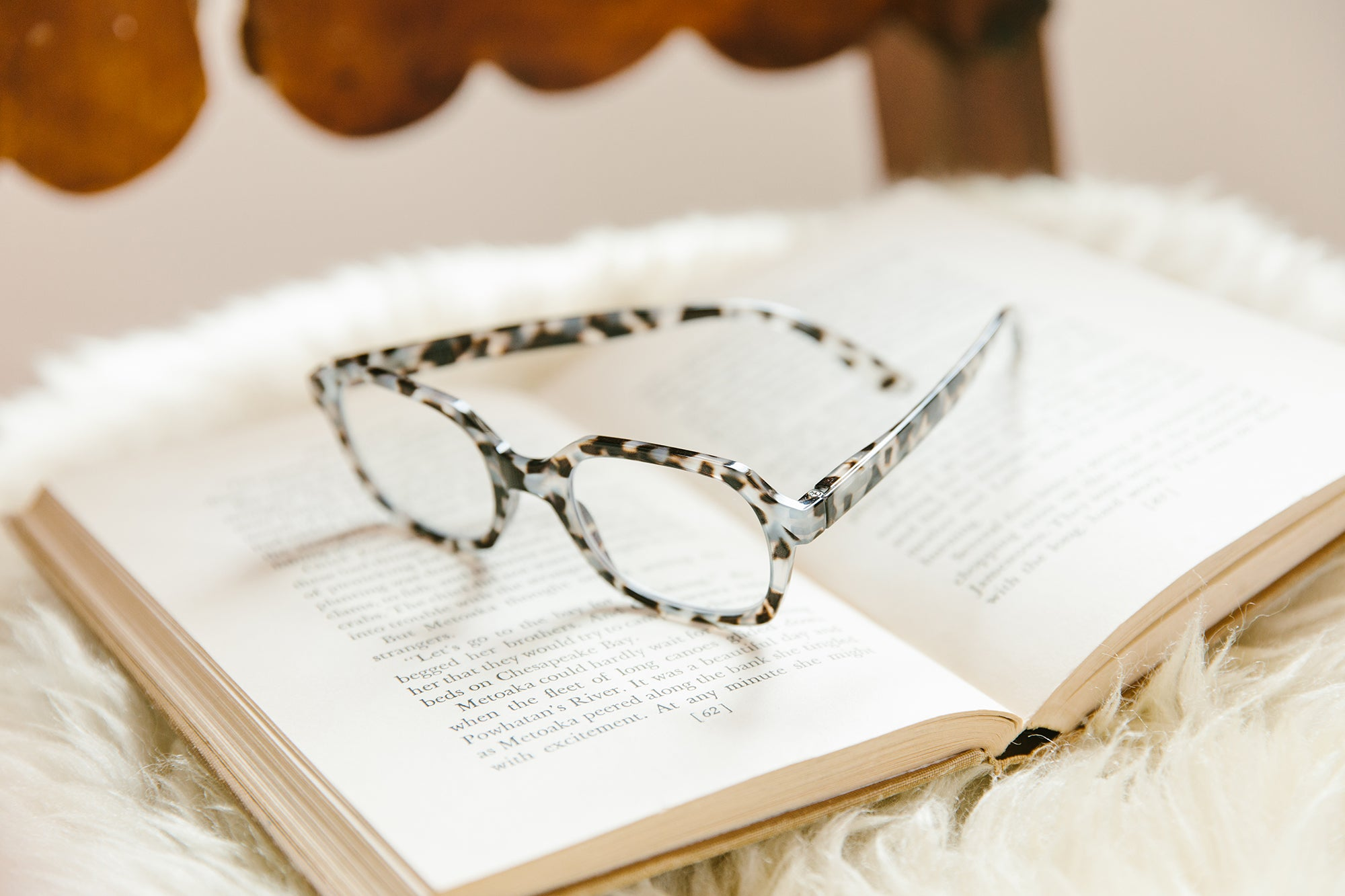 Peepers gray tortoise reading glasses sitting on an open book