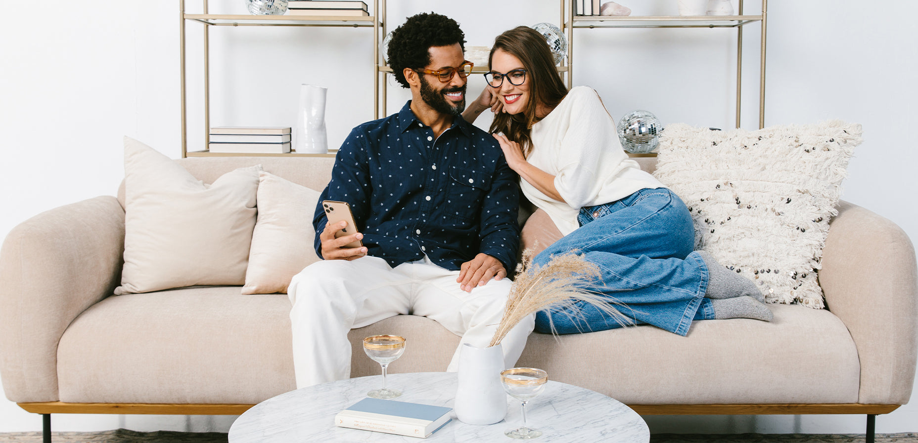 Man and woman sitting on a couch wearing Peepers blue light glasses