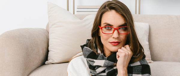 Woman in scarf wearing red Peepers reading glasses