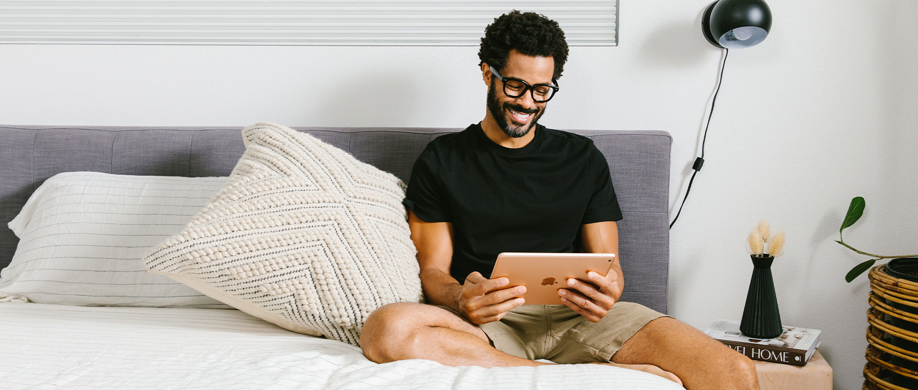 Man wearing Peepers reading glasses in bed while looking at a tablet