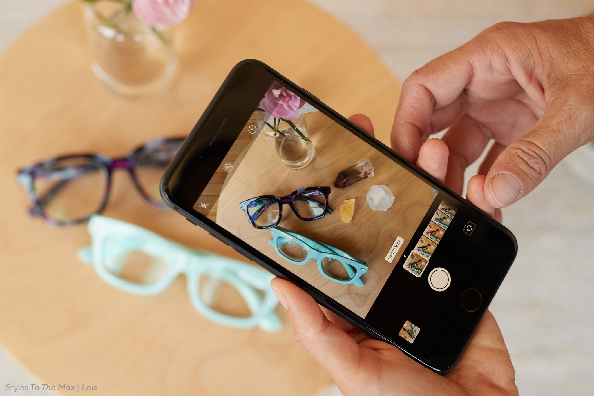 Close-up of a person's hands taking a photo of Peepers To The Max and Lois blue light reading glasses on a table
