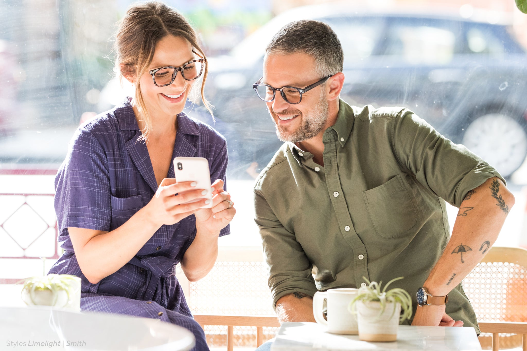 Man and woman looking at a smart phone at a cafe in front of a window wearing Peepers Limelight and Smith blue light reading glasses
