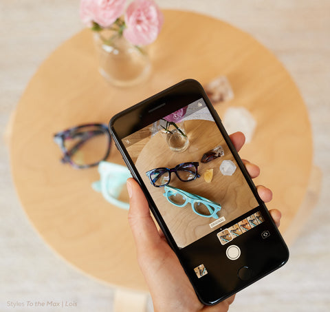 A smartphone screen showing Peepers To the Max and Lois blue light reading glasses arranged on a table