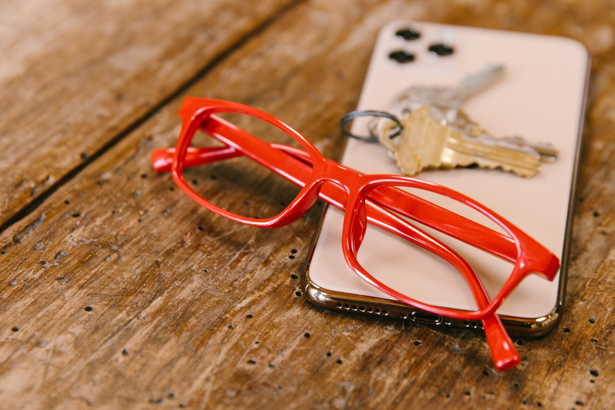 Peepers red reading glasses sitting on a phone and keys