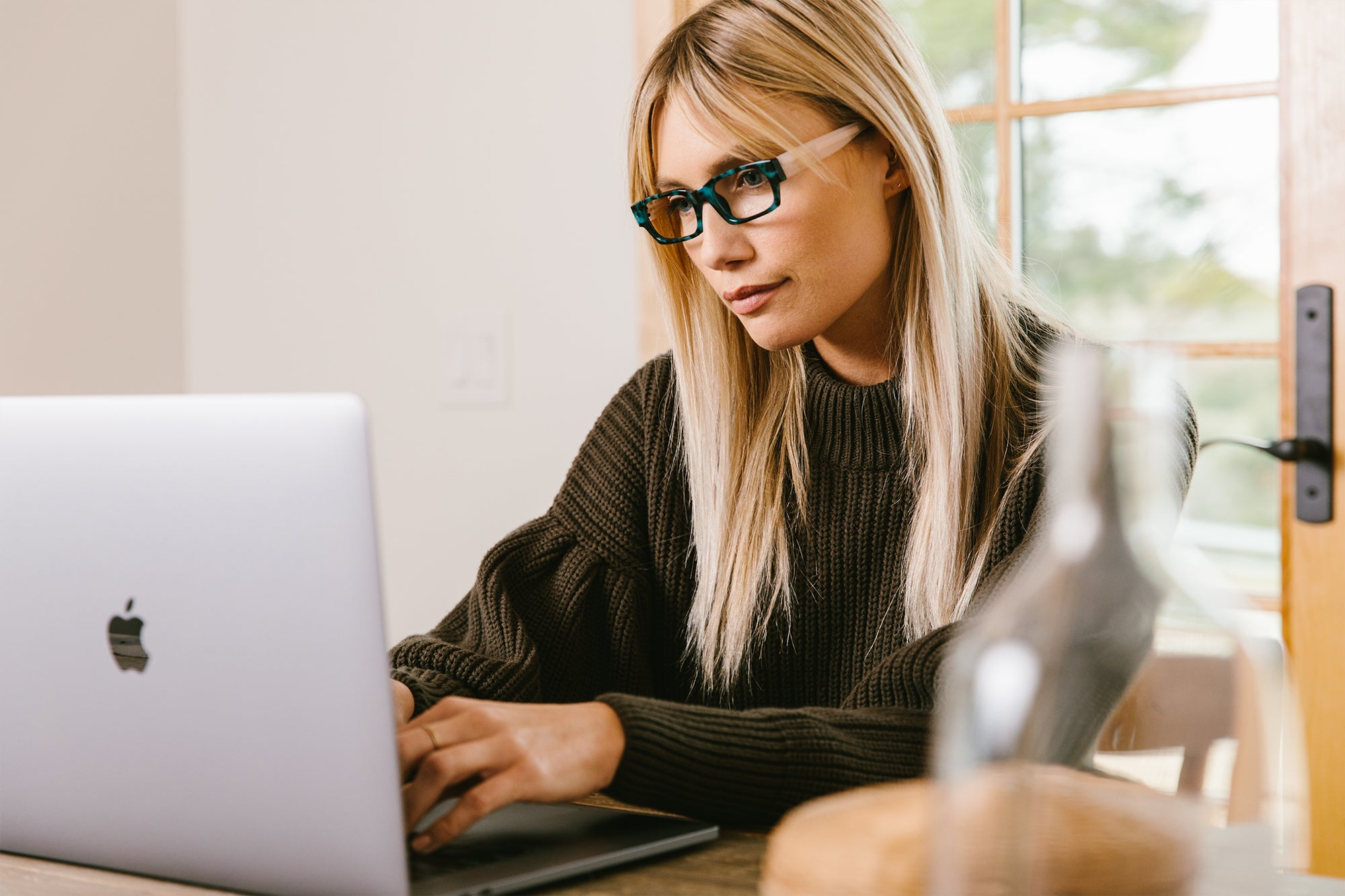 Woman wearing Peepers blue light reading glasses while working on laptop