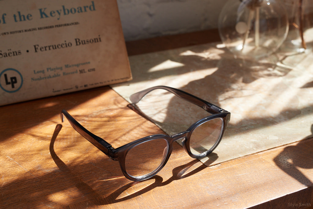 Peepers Smith blue light reading glasses in gray sitting in shadows on a wood desk by a glass vase