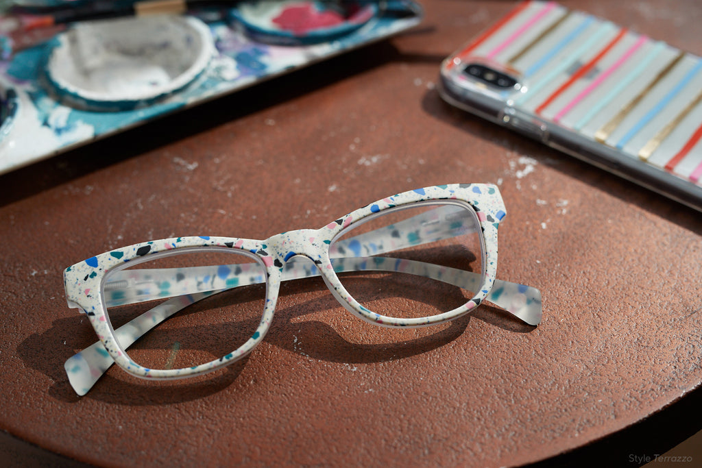Peepers Terrazzo blue light reading glasses folded on a table by a phone and art paint