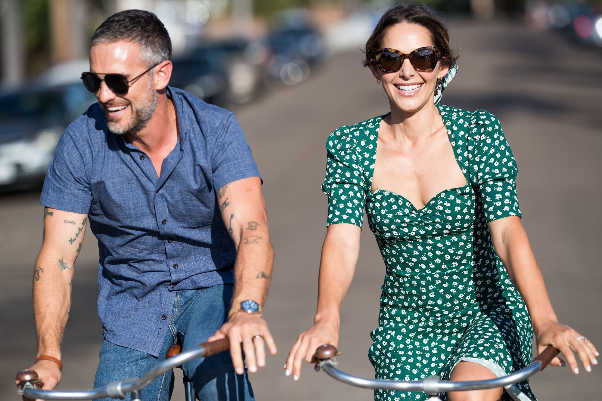Man and woman in sunglasses riding bikes