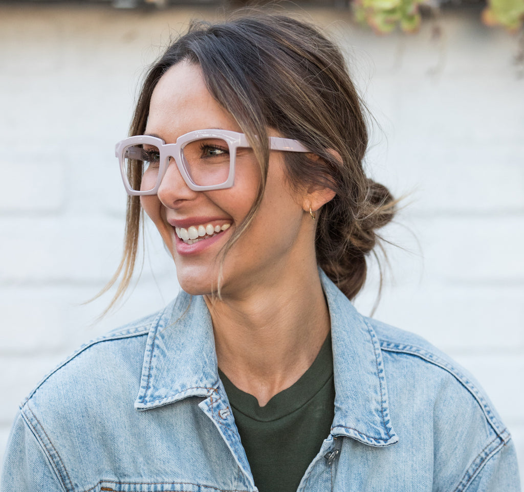 Brunette woman with hair pulled back and jean jacket wearing Peepers Standing Ovation blue light reading glasses in taupe