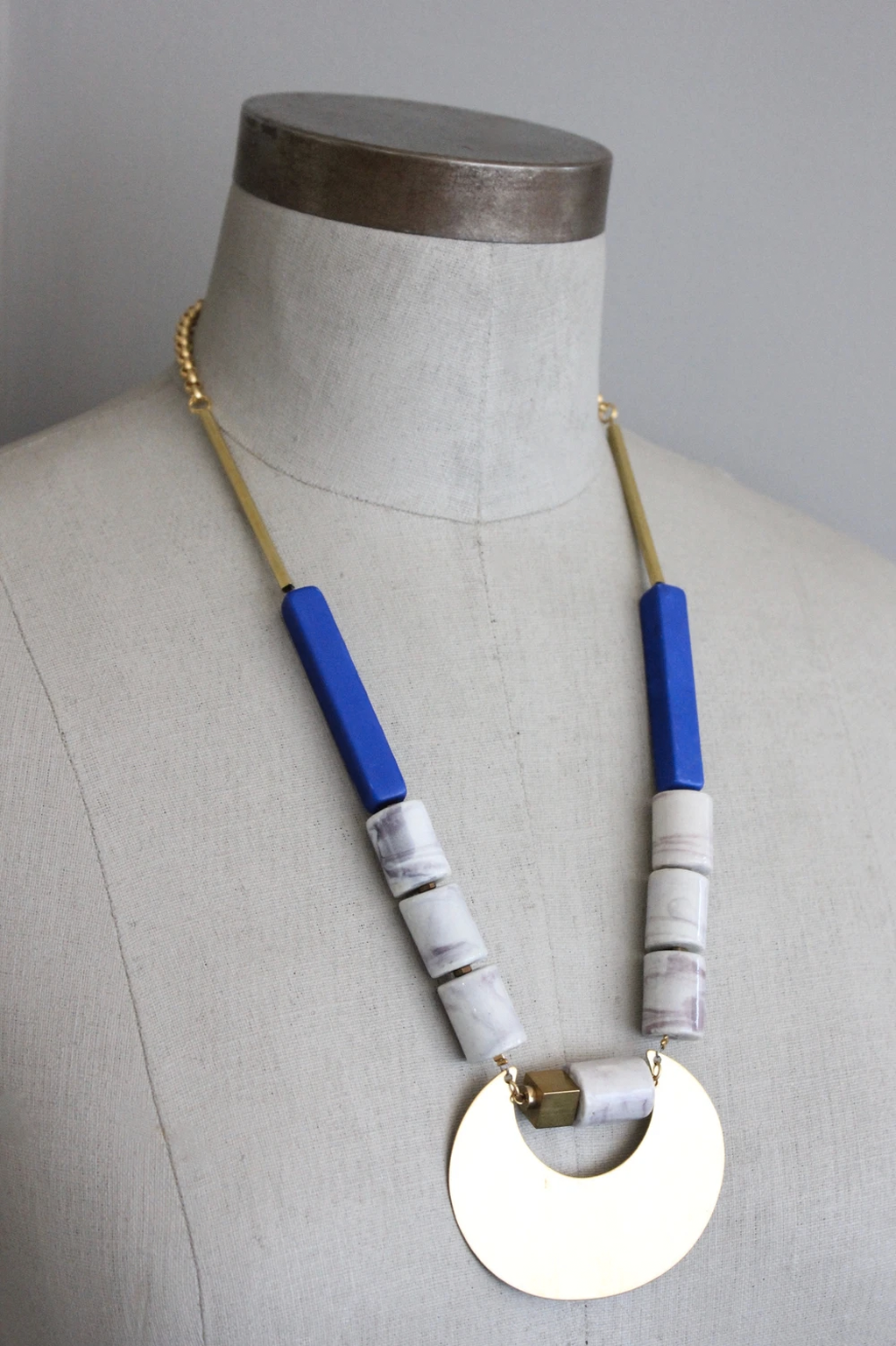 Brass half moon with blue and white porcelain necklace