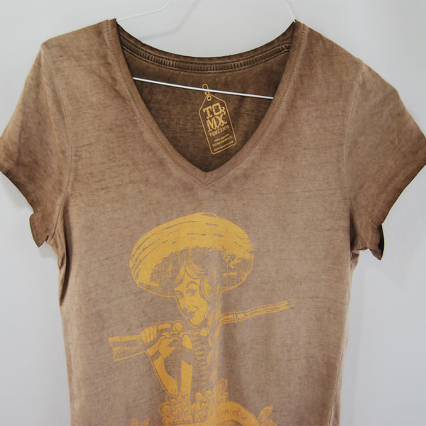 T-Shirt Adelita Brown V Neck for Women, This T-Shirt is a tribute to the Mexican women in the Revolution era. These women were fundamental to this movement empowering the Mexican society. This is an invitation to the actual generation of women all over the world to keep fighting for human rights.  Brown washed color printed in yellow tone.