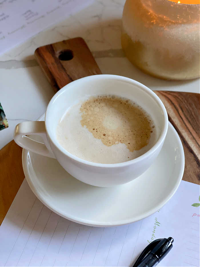 Coffee in white cup with meal planning worksheet