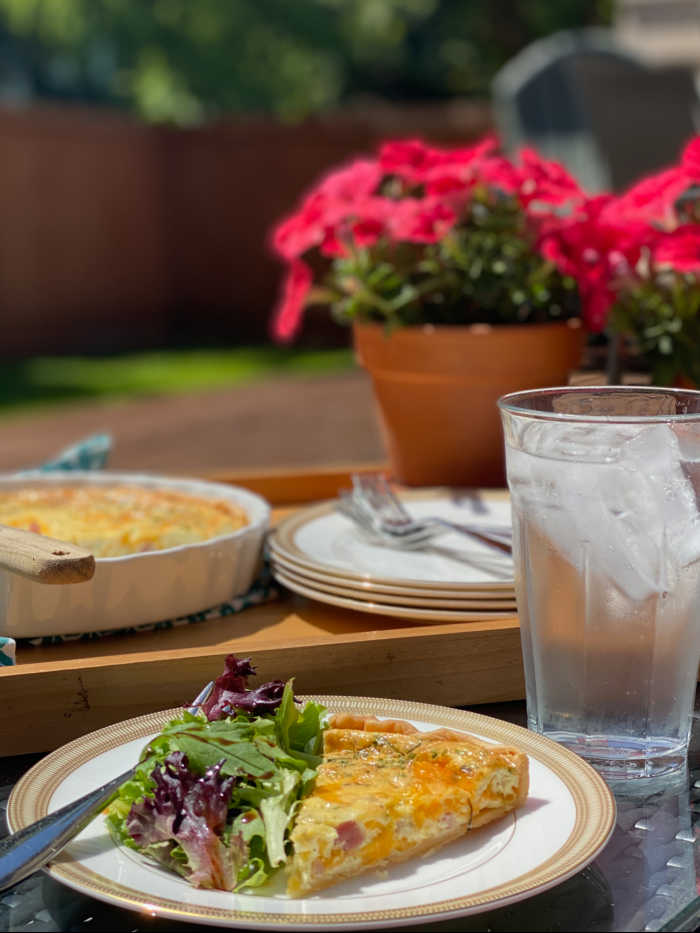 Quiche and iced water on table with flowers