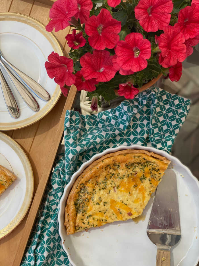 Overhead photo of quiche in pan with spatula, flowers and plates
