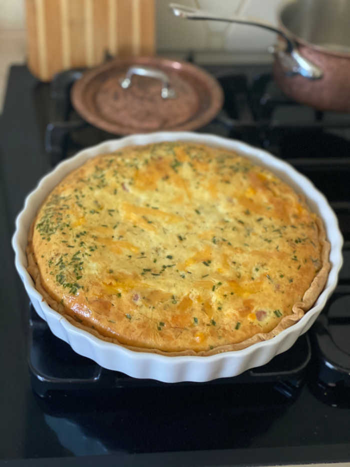 Quiche in a tart pie pan on a stovetop
