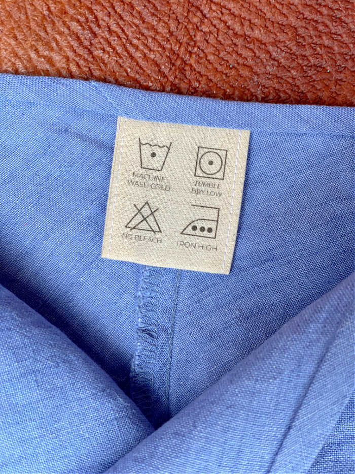 Photo of cotton care label in a blue shirt collar