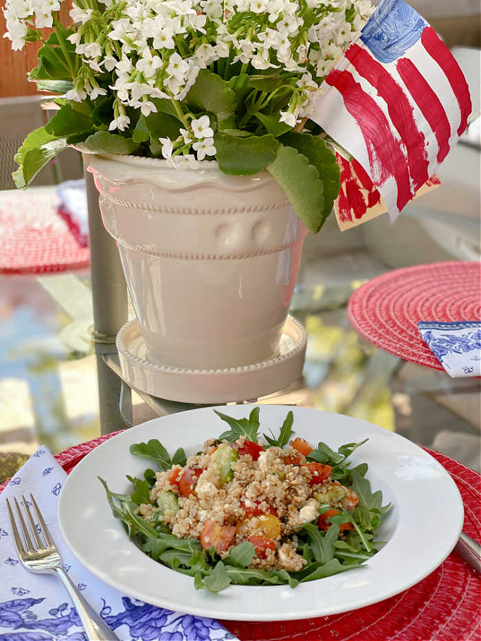 Quinoa salad in a bowl with a planter and American flag on a table