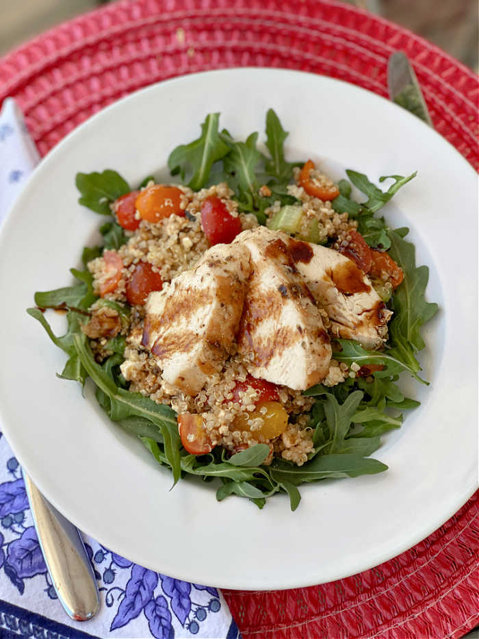 Sliced chicken on top of quinoa salad and arugula leaves