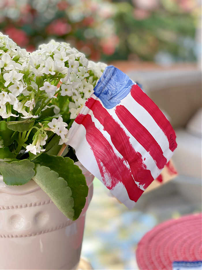 Photo of paper painted American flag in a flower pot on a glass table